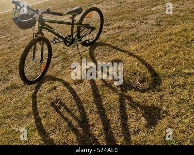 Bicycle with helmet in sunshine on grass with long shadows - Stock Image