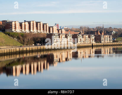 Apartment buildings on Newcastle quayside reflected in the river Tyne, north east England, UK - Stock Image