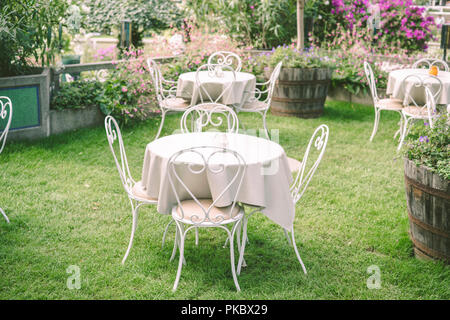Romantic garden setting with vintage furniture and table cloth surrounded by flowers - Stock Image