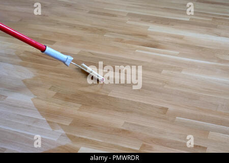 Varnishing lacquering an oak parquet floor by paint roller first layer. - Stock Image
