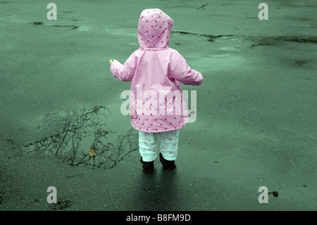 little girl toddler two years old playing pink raincoat wet rainy day cute positive outside female fun jacket weather - Stock Image