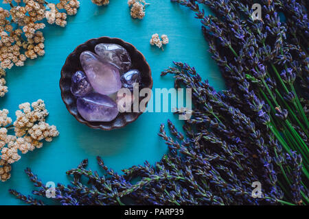 Polished Amethyst with Lavender and Flowers on Turquoise Table - Stock Image
