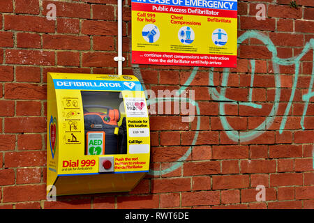 Public defibrillator emergency life saving equipment mounted on outside wall, Okehampton, Devon, England - Stock Image