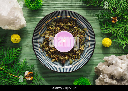 Dried Patchouli Herb and Purple Candle with Smoky Quartz and Greenery - Stock Image