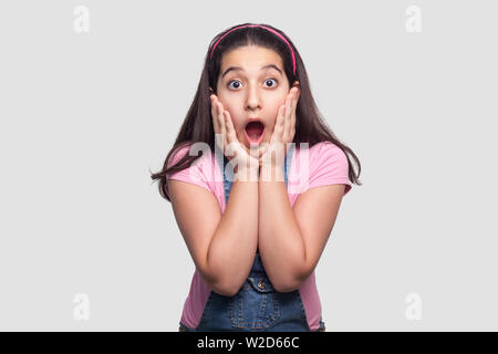 Portrait of surprised beautiful brunette young girl in casual pink t-shirt and blue overalls standing with hands on face and looking with amazed face. - Stock Image