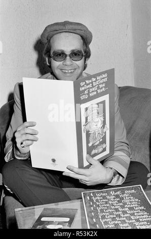 Elton John pictures on 24th March 1977, a day before his 30th birthday, which is on the next day, 25th March.  Caption from the time says¿.  'Top pop singer Elton John is 30 years of age tomorrow. (Friday) Elton who is at present in London producing an album for one of his new groups, intends to have a quiet day of celebration, despite the delivery of these mammoth bottles of Champagne (see other frames in this set for the Champagne Bottles).  The cards and Good Wishes have already arrived for Elton for his 30th birthday, but he himself feels a little sad and is counting the hours as he sees h - Stock Image