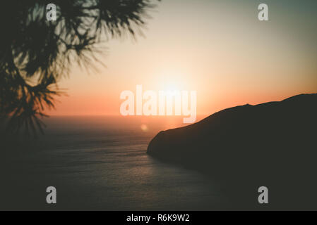 Evening silhouette of island at rays of sunset. Vintage effect - Stock Image