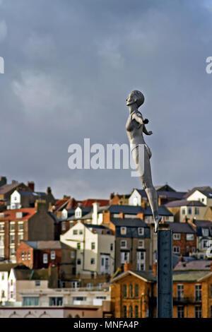 Scarborough's Diving Belle statue stands out against the crowded backdrop of the town's Bland's Cliff. - Stock Image