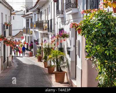 Estepona old town with white washed buildings and traditional potted geraniums, family exploring the quiet historic streets Estepona, Málaga, Spain - Stock Image