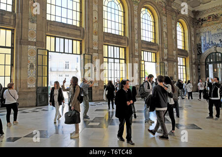 People looking at blue azulejo tiles in the Central Hall of Sao Bento railway station train station in the city of Porto Portugal Europe KATHY DEWITT - Stock Image
