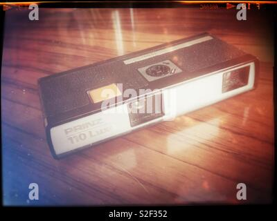 A vintage pocket camera from ca 1972 in the redundant 110 film format on a mahogany table. Retro treatment. - Stock Image
