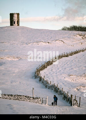 A man walking his dog in the snow near Solomon's Temple also called Grinlow Tower the Victorian Fortified hill - Stock Image
