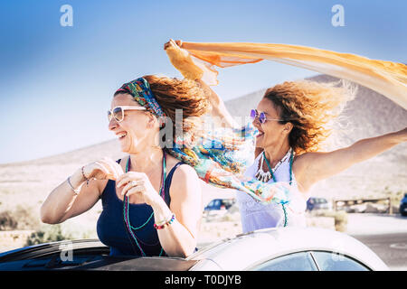 Couple of middle age caucasian woman cheerful and laughing enjoying the travel and the vacation with convertible car and playing with the wind for fre - Stock Image