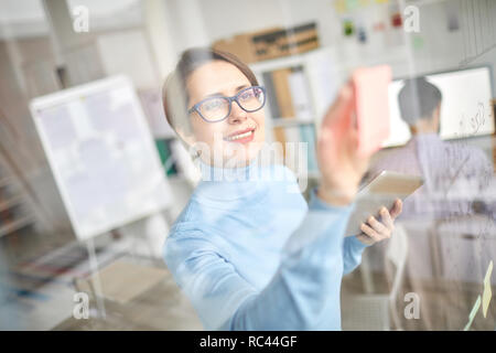 Happy young manager sticking notepaper on transparent board while organizing work for the following week - Stock Image