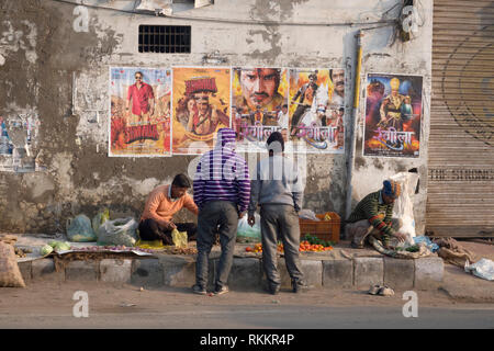 Street market vendors selling vegetables in front of Bollywood posters in Amritsar, India - Stock Image