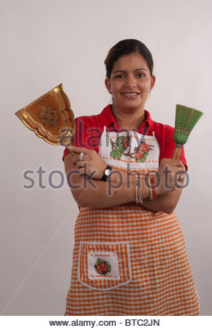 Maid posing with dustpan and whisk broom - Stock Image