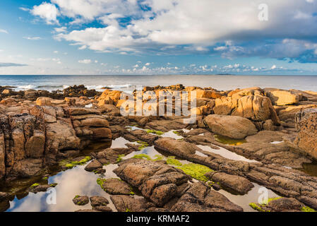 The orange-red granite of the Thorr Pluton on the foreshore at Bloody Foreland, County Donegal, with Tory Island - Stock Image