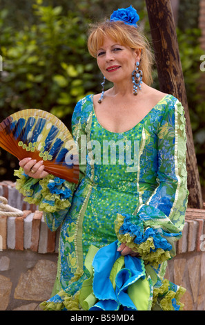 Beautiful blond middle aged Spanish woman in traditional costume with fan ( abanico ) Costa del Sol, Andalucia, - Stock Image