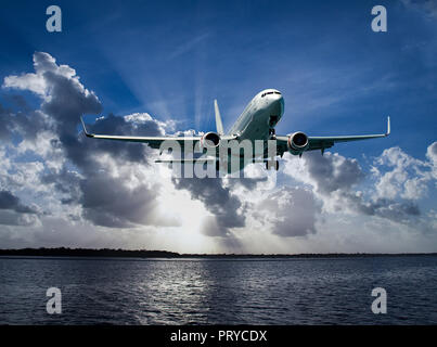 Colourful Australian Cloudscape Seascape with an airborne passenger jet airliner flying high in  white coloured cumulonimbus cloudy steel blue sky. - Stock Image