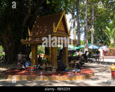 Local people worshipping at small shrine part of larger Ya Tep Shrine Independence Gardens Siem Reap resort town in northwest Cambodia Asia - Stock Image
