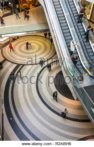 Shoppers on escalator and circles in The Eaton Centre a multi level downtown shopping mall in Toronto Ontario Canada - Stock Image