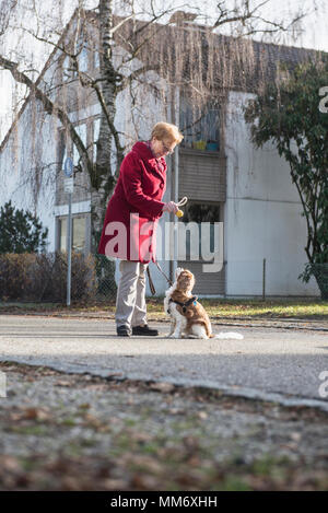 Old woman and dog standing on the street with toy - Stock Image