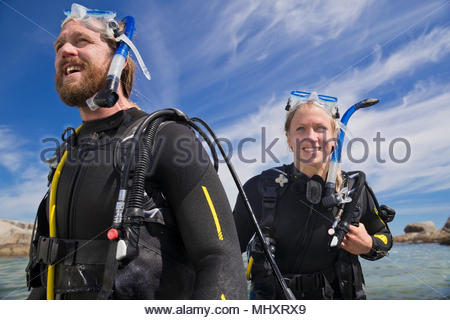 Portrait of happy scuba diver man and woman walking out of ocean after dive - Stock Image