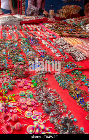 Large selection of a range of style of earrings and jewellery on a market stall for sale. - Stock Image