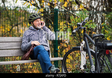 A senior man with electrobike and smartphone sitting on a bench outdoors in town in autumn, making a phone call. Copy space. - Stock Image