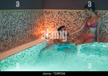 Happy young couple doing a swimming pool spa center day - Romantic lovers having a tender moment in vacation resort wellness hotel - Stock Image