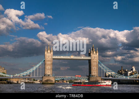 Tower Bridge wide view landscape with London red bus crossing bridge and 'City Cruises River Boat' navigating a turn on the River Thames, viewed from a RB1 Commuter River Boat in late afternoon sun with dramatic spring sky Southwark London UK Panorama Vista City View attraction with clear blue sky. Tower Bridge is a combined bascule and suspension bridge in London, built between 1886 and 1894. The bridge crosses the River Thames close to the Tower of London and has become an iconic and enduring symbol of London England Great Britain UK - Stock Image