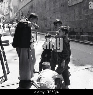 1950s, Hong Long, street trader showing some young children his soft toys, - Stock Image