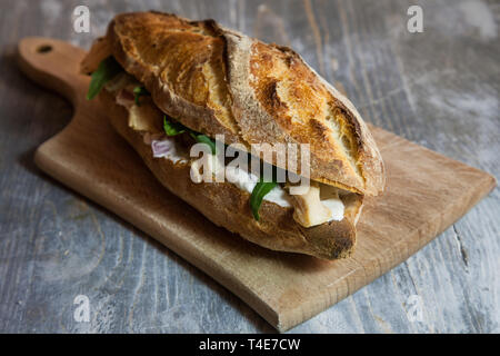 Chicken sanwdich with cream cheese in a French baguette, with some slices of rucola salad and chicken dressing on a rustic wooden table. This sandwich - Stock Image