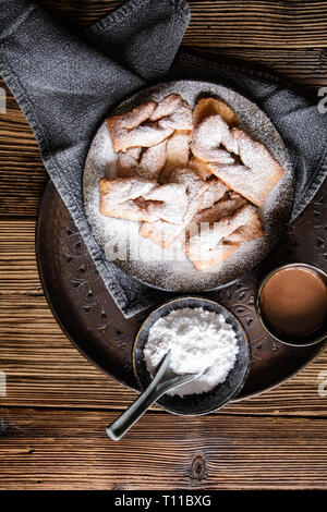 Homemade Calzones rotos – Chilean fried pastry, sprinkled with powdered sugar and served with hot chocolate - Stock Image