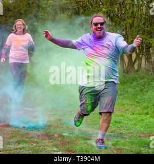 Large overweight male runner laughing and arms outstretched being covered in paint on Macmillan cancer charity 5K color fun run. - Stock Image