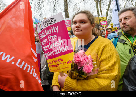 London, UK. 16th March 2019. Woman in crowd with pink roses. Thousands march through London on UN Anti-Racism day to say 'No to Racism, No to Fascism' and that 'Refugees Are Welcome Here', to show solidarity with the victims of racist attacks including yesterdays Christchurch mosque attack and to oppose Islamophobic hate crimes and racist policies in the UK and elsewhere. The marchers met in Park Lane where there were a number of speeches before marching to a rally in Whitehall. Marches took place in other cities around the world including Glasgow and Cardiff. Peter Marshall/Alamy Live News - Stock Image