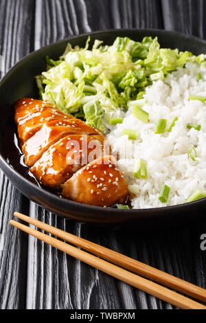 Asian teriyaki chicken recipe with rice side dish and salad close-up on a plate on the table. vertical - Stock Image