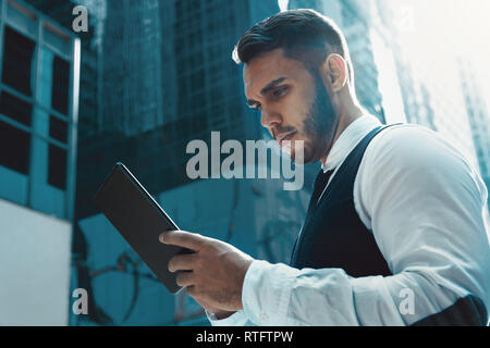 Businessman stands with tablet computer in city and read something - Stock Image