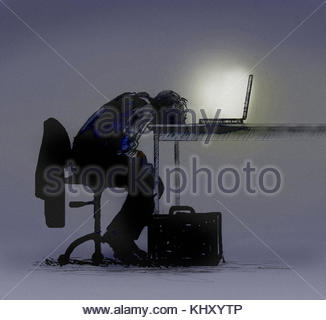 Exhausted businessman slumped over laptop computer - Stock Image