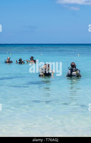 Divers in full SCUBA gear prpare for a dive in West Bay Roatan Honduras. - Stock Image