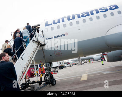 People boarding a Lufthansa jet - Stock Image