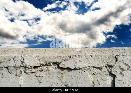Crumbling white brick cement wall with flaking paintwork and a blue sky with clouds for construction backgrounds - Stock Image