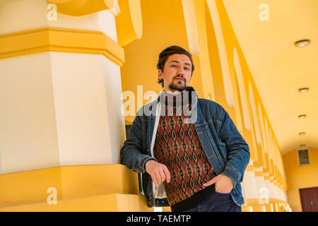 Portrait of a stylish handsome young man with a jaket outdoors.  A serious man wearing a jaket looking confident at the camera. - Stock Image