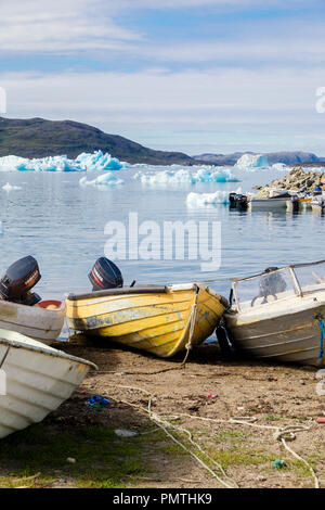 Small fishing boats in Qajaq Harbour with icebergs offshore in summer. Narsaq, Kujalleq, South Greenland - Stock Image