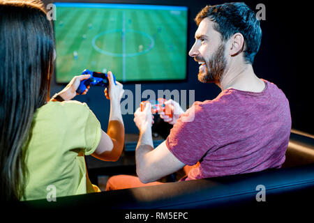 Young excited couple playing football game with gaming console sitting on the couch at the playing club - Stock Image