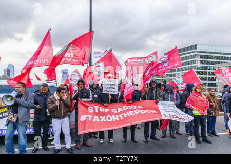 London, UK, 04th April 2019. Minicab drivers block the road on London Bridge protesting against the congestion change on private hire minicabs.  The demonstrators hold and wave flags and placards of UPHD (United Prive Hire Drivers) and IWGB (Independent Workers Union of Great Britain). Credit: Graham Prentice/Alamy Live News - Stock Image
