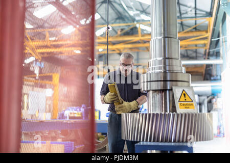 Engineer fitting spindle into heated gear wheel in gearbox factory - Stock Image