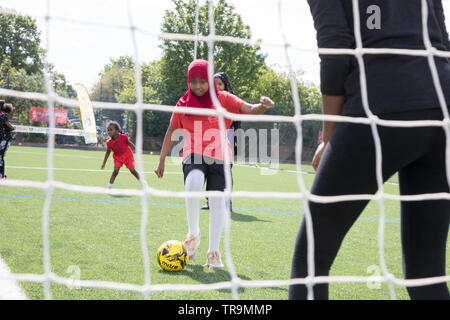 A Muslim girl with headscarf shoots a football at goal during a training session - Stock Image