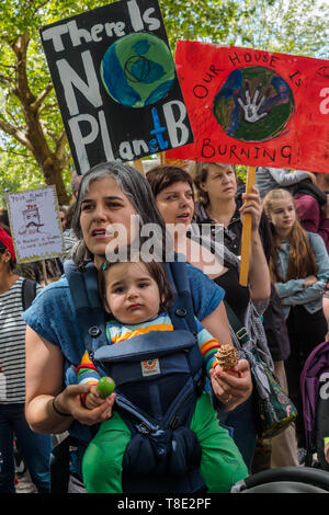 London, UK. 12th May 2019. People wait for the start of the march by several thousand mothers, children and some fathers behind 11-year-olds and 3 giant push chairs with stilt walkers from Hyde Park Corner to a rally filling Parliament Square, backing Extinction Rebellion's call for the drastic and urgent action needed to avert the worst consequences of climate change, including possible human extinction. Our politicians have declared a climate emergency but now need to take real action rather than continuing business as usual which is destroying life on our planet. Peter Marshall/Alamy Live N - Stock Image