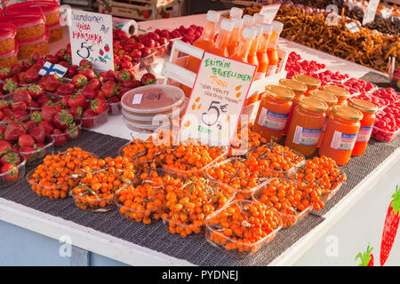 20 September 2018: Helsinki, Finland - Sea Buckthorn berries for sale at a farmer's market in the Market Square on the waterfront. - Stock Image